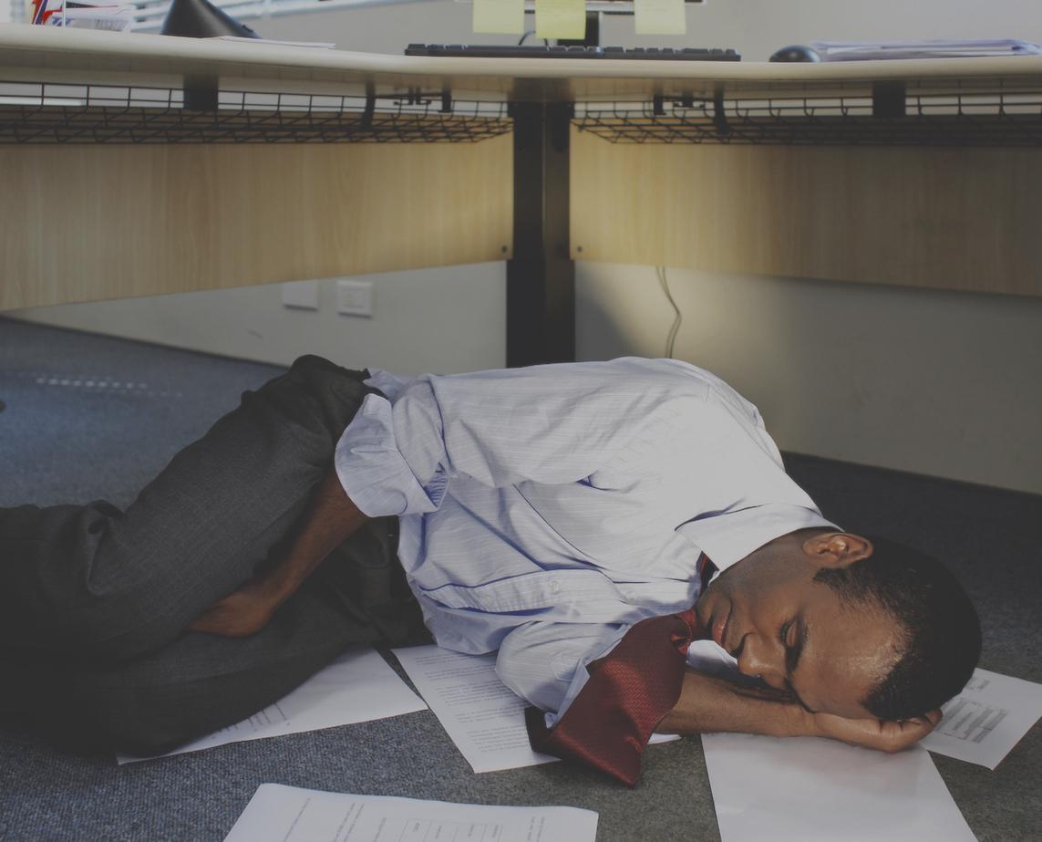 adult-man-sleeping-under-desk-papers-on-floor