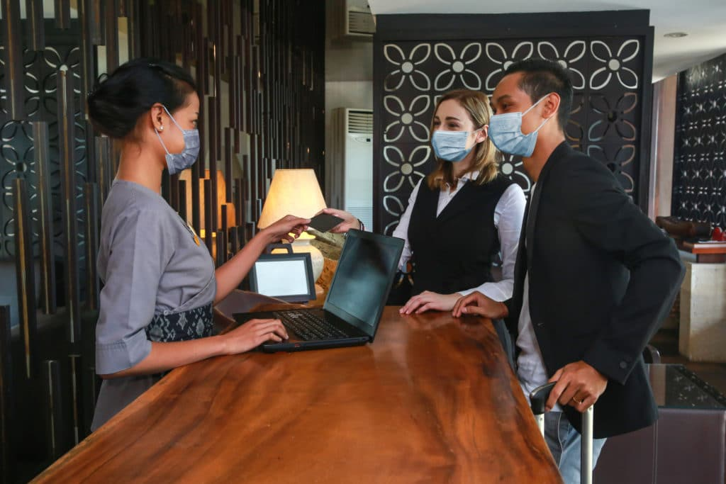 Couple And Receptionist At Counter In Hotel Wearing Medical Masks As Precaution Against Virus. Couple On A Business Trip Doing Check In At The Hotel