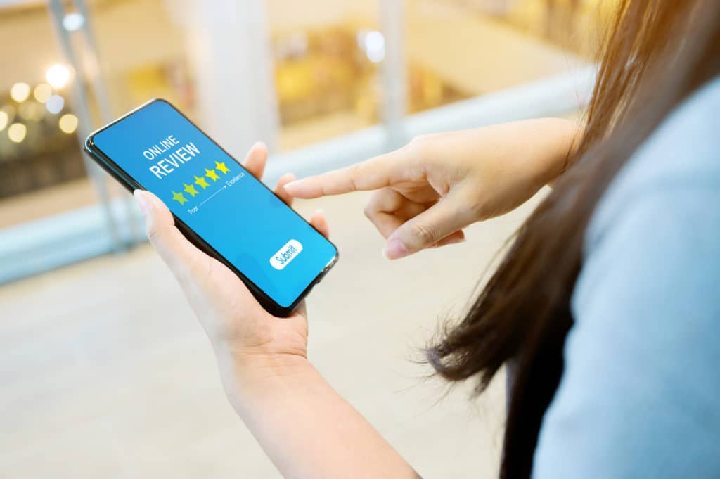 Online Review Rating Business Concept. Woman Using Her Mobile Smartphone
