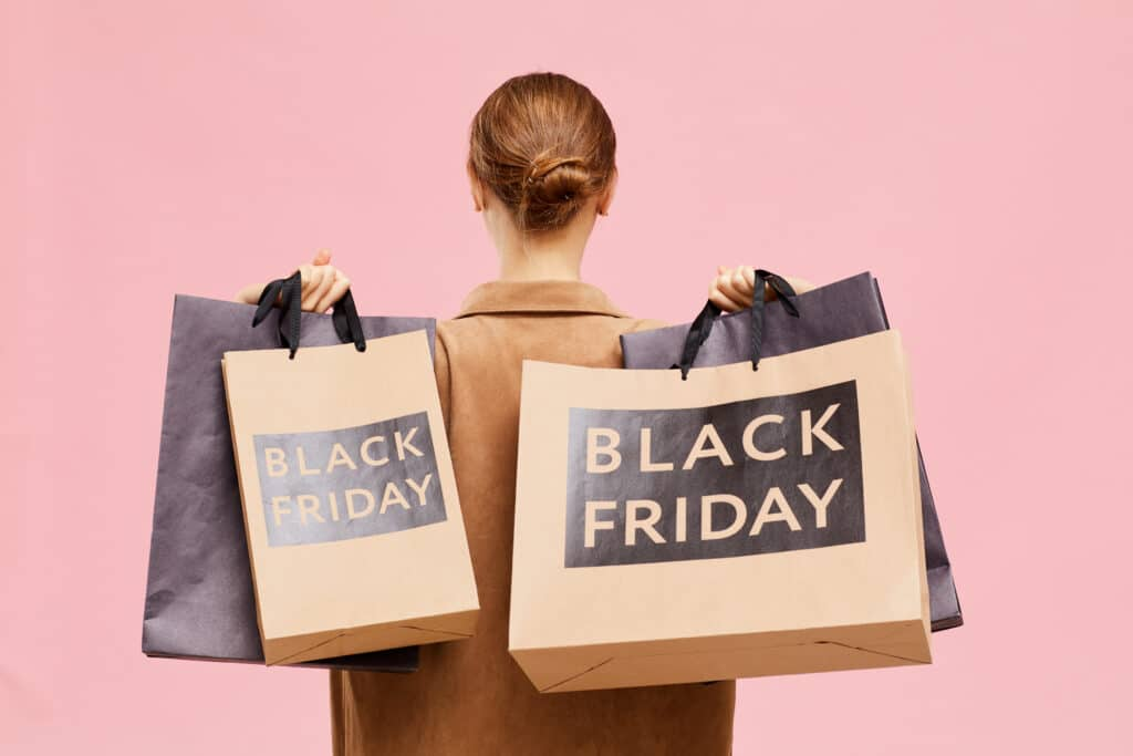 Rear View Of Unrecognizable Woman With Hair Bun Carrying Black Friday Paperbags On Shoulders While Leaving Store
